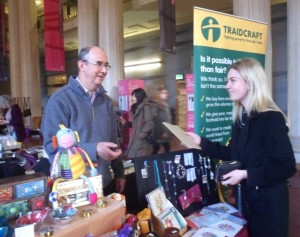 Roger of the Beehive shop serves customers at the Fair Trade Fair